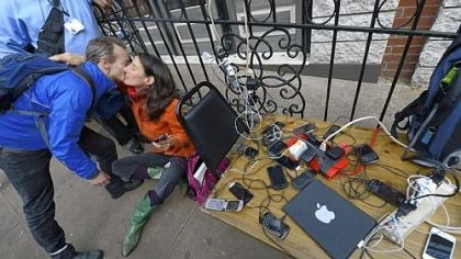Waiting to have laptops charged People hug as they wait to have phones and laptops charged at a generator set up in the West Village Nov. 1 as New Yorkers cope with the aftermath of Hurricane Sandy.