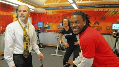 XRKade at the Y Jay Hope, left, associate executive director of the Penn Hills YMCA, and fitness coach Lomel Patterson, right, demonstrate an interactive snowboarding video game in the new XRKade at the Penn Hills YMCA on Friday. In the background is XRKade director Andrea Oh. The XRKade, a new facility at the Penn Hills YMCA, uses video games to attract children 9-12 to physical activity.