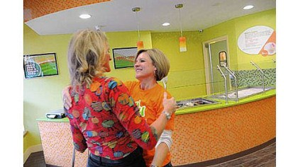 Yogli Mogli Ellie Hall, right, embraces Lynne Jones of Colorado as they prepare to open Yogli Mogli yogurt shop on Washington Road in Mt. Lebanon Saturday. Ms. Hall is the widow of the late Brian Hall, co-owner of the business, who died recently in a small plane crash. Ms. Jones is the wife of the other co-owner.