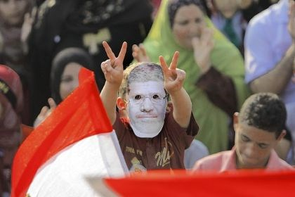 young supporter of Morsi A young supporter of Egypt's ousted President Mohammed Morsi flashes victory signs as he puts on a mask with his picture during a protest Tuesday in Cairo.
