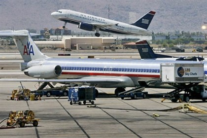 Airline Merger 1 A US Airways jet takes off in 2008 as an American Airlines jet is prepped for takeoff at Sky Harbor International Airport in Phoenix.