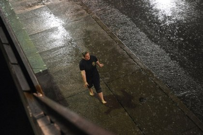Daily0417j.jpg A pedestrian walks barefoot through heavy rain outside Lawrence Hall along Forbes Avenue in Oakland.