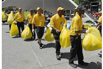 "Clean Team members from the Pittsburgh Downtown Partership carry their distinguishable yellow bags of litter at the launch of the ""Caught Doing Good!"" campaign in Market Square."