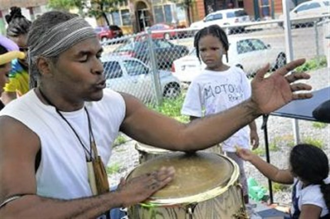 Storyteller Gregory E. Wood leads a drum circle during the Ujamaa Collective's Children's Literary Festival in the Hill District.