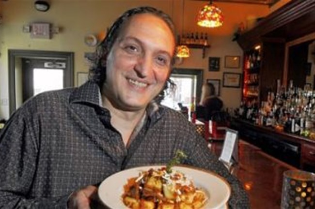 Michele Savoia, owner of Dish Osteria and Bar, holds a plate gnocchi al ragu di cinghiale (gnocchi with wild boar) at the South Side restaurant.