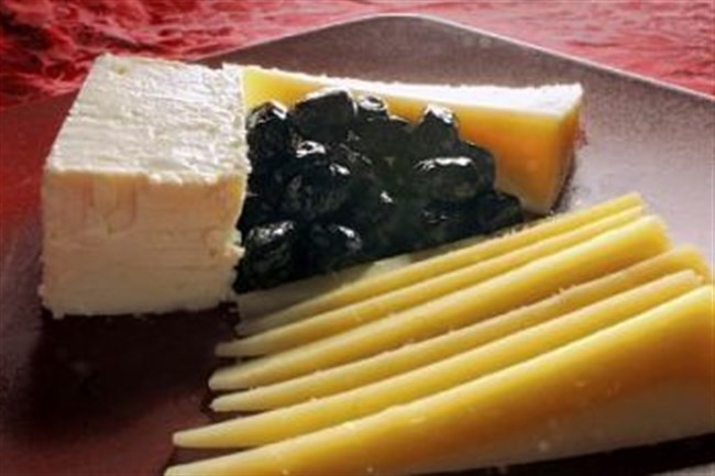 Cheeses from Greece, clockwise from left: Feta, kefalotiri and graviera with oil-cured olives.