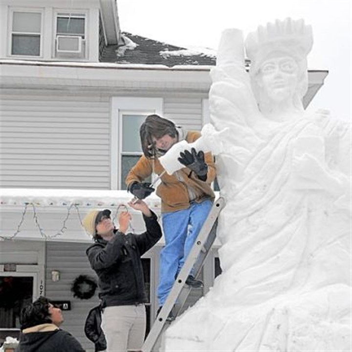 15-foot-tall, snow Statue of Liberty From top, Minhas Hameed, Umair Akhlas and Mohsin Hameed top off a 15-foot-tall Statue of Liberty made of snow in the front yard of their home Monday in the 1100 block of Fourth Avenue in Beaver. The families, who are Christians, are recent arrivals in the U.S., leaving their native Pakistan due to religious violence.