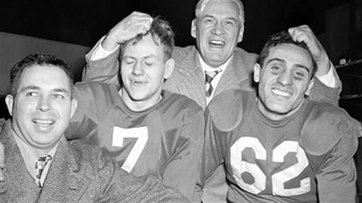 1947 title game Coach Jimmy Conzelman musses the hair of Charley Trippi, right, and Elmer Angsman after the 1947 title game.