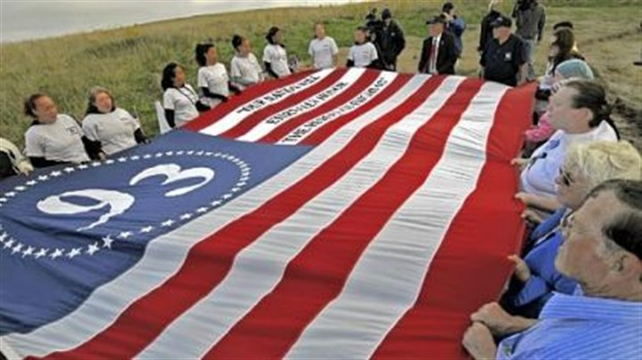 9/11 in Shanksville: Flag North Plainfield, N.J., cheerleaders and friends unfurl their tribute flag before the start of the memorial service for the passengers of Flight 93 at the temporary memorial near the crash site.