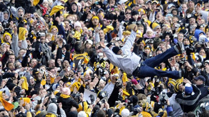A happy dive Steelers' safety Ryan Clark leaps from his vehicle into the waiting arms of Steelers fans lining the Boulevard of the Allies.