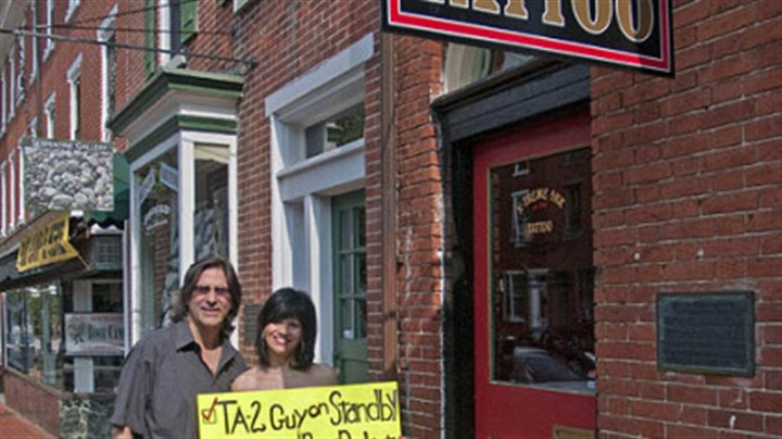 A sign of the times Rose Ann Belluso and her husband, Jim, stand in front of X-Treme Ink Tattoo in West Chester, Pa., with the sign Rose Ann used to get her back signed by Paul McCartney during a concert Sunday night in Philadelphia.