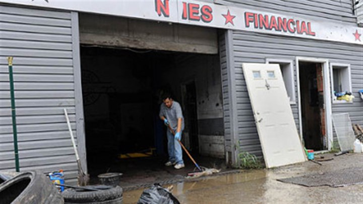 Aftermath Rick Ibrahim sweeps out water Saturday from Best Auto Mart in the South Hills. There were several feet of water inside his store Friday after strong storms caused a flash flood.