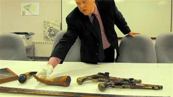 Alan Gutchess Fort Pitt Museum Director Alan Gutchess works with the display of powder horns and pistols as the museum prepares to reopen Saturday.