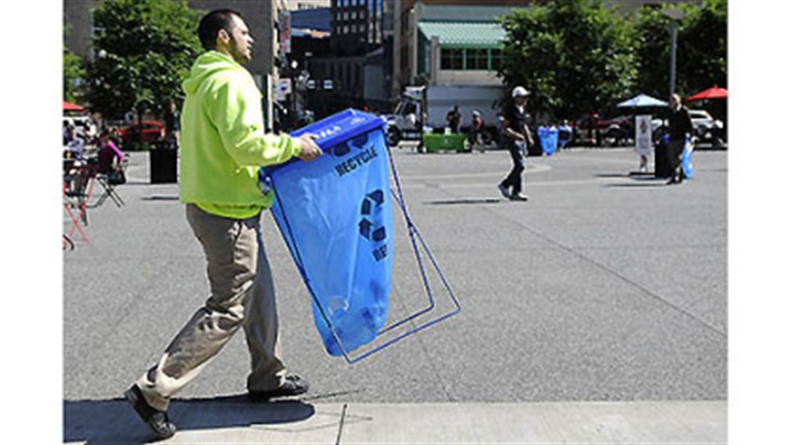 "Anti-litter campaign City of Pittsburgh environmental services worker Joseph Cirigliano sets up a trashcan yesterday in Market Square before Mayor Luke Ravenstahl's announcement of the ""Don't Trash My Turf!"" campaign."