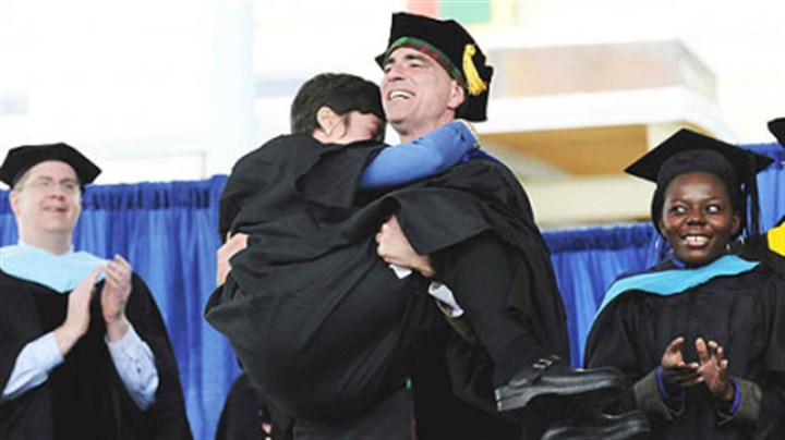 At CMU graduation To a rousing ovation, Randy Pausch carries his wife, Jai back to their seats after giving the charge to the graduates at CMU's 111th commencement ceremony May 18.