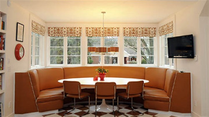 Banquette A built-in banquette done in camel leather surrounds a large oval Saarinen table.