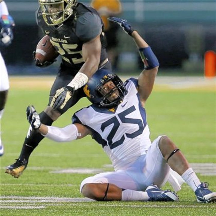 Baylor rambles on Baylor running back Lache Seastrunk, top, is pulled down by West Virginia safety Darwin Cook.