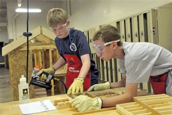 Beattie Tech 2 Andrew LaMay 14, of McCandless, left, and Alex Kosylo, 15, of Shaler use a nail gun to assemble a model house in the carpentry section of the Beattie summer camp last week.