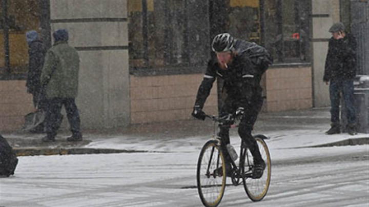 biking snow pittsburgh A bicyclist rolls down Liberty Avenue in Downtown Pittsburgh this morning.