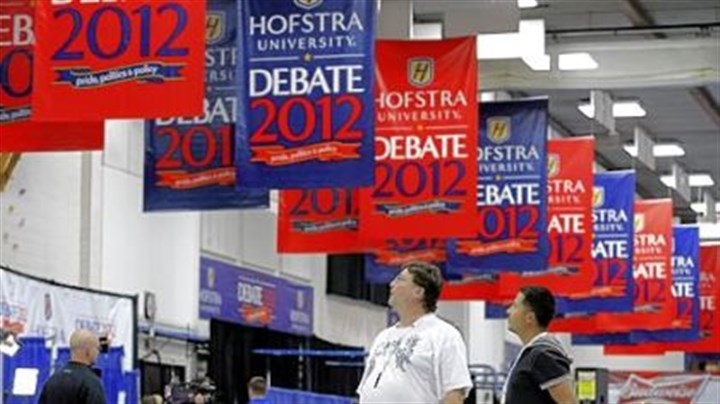 Billy Koske and Jose Reyes Billy Koske, left, and Jose Reyes look at signs hanging Monday in the media center before tonight's presidential debate at Hofstra University in Hempstead, N.Y.