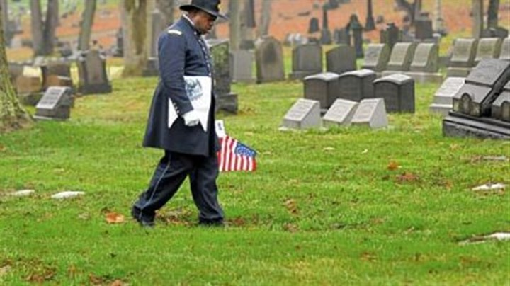 Black troops remembered Jeffrey Burton, portraying Major Martin R. Delaney of the 104th USCT (U.S. Colored Troops) and the first black field officer in the Civil War, walks through Allegheny Cemetery in Lawrenceville on Sunday looking for USCT soldiers' graves to honor them with a flag.