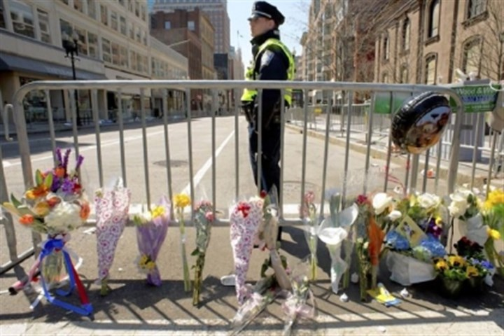 Boston police A Boston police officer stands guard Tuesday at a memorial site at Boylston and Arlington streets, which was along the course of the Boston Marathon a few blocks from where two explosions struck near the finish line.