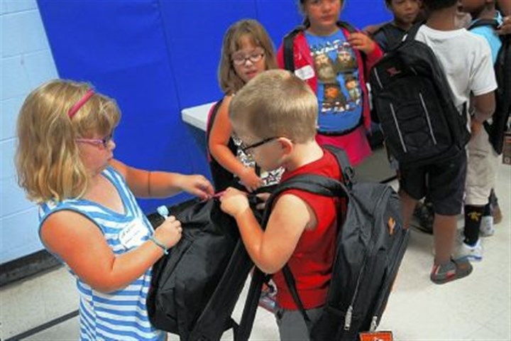 Bree Benson Bree Benson, 5, left, and her twin brother, Chase, look over a new backpack they received at Huntington Bank's fifth annual backpack program at the Homewood Salvation Army Center.