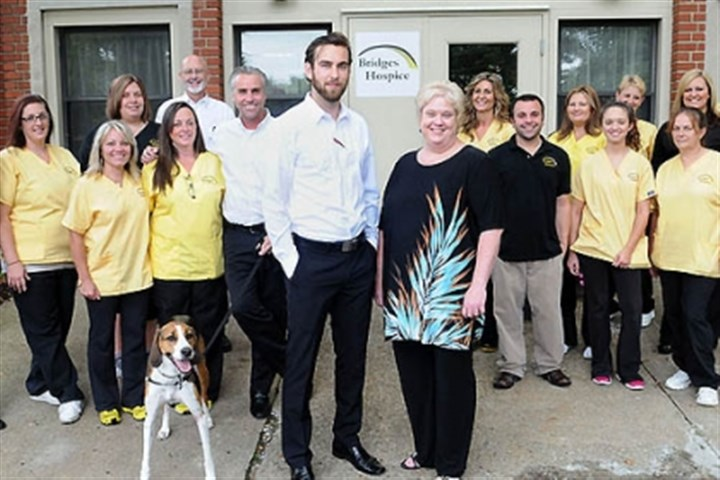 Bridges Hospice Executive Director Christian Vagley, left front, owner Krista Cox, company dog Luca and staff members of Bridges Hospice at their Harmar facility.