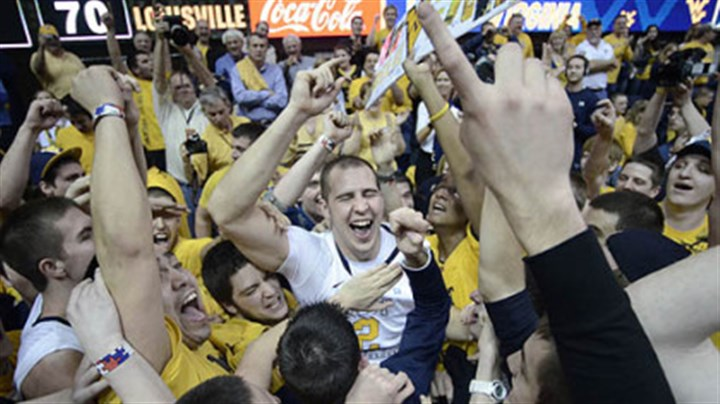 Cam Thoroughman West Virginia's Cam Thoroughman, center, celebrates with fans following a 72-70 win against Louisville today in Morgantown, W.Va.