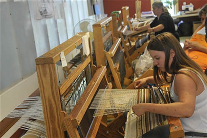 caritas3 Jennifer S. works with alpaca yarn on a loom at the Caritas Weaving Loft outside New Castle in July. The finished fabric will be crafted into a tote bag.
