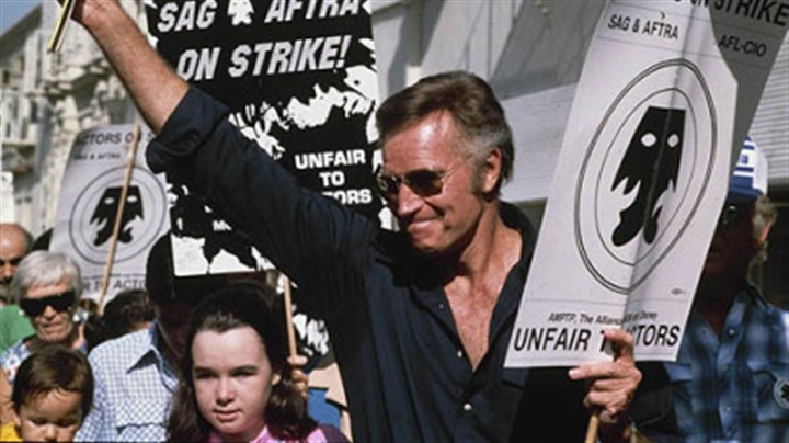 Charlton Heston on SAG picket line Charlton Heston waves to fans while walking the picket line outside Paramount Studios in Hollywood during the Screen Actors Guild and American Federation of Television and Radio Artists strike in August of 1980.