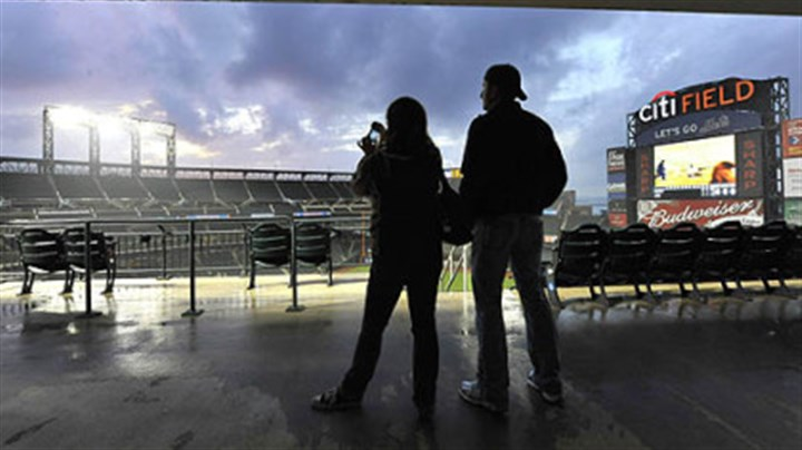 Citi Field Mary Spadoni, from the Astoria neighborhood of the Queens borough of New York, photographs the clearing storm clouds over Citi Field with her friend, Matthew Thompson, also from Astoria.