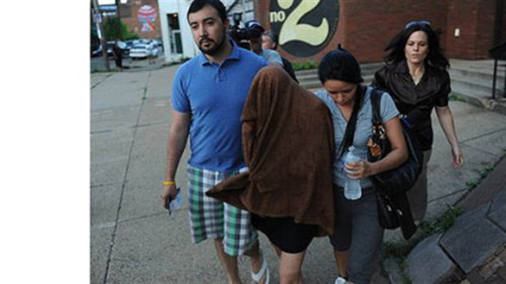 Claudia Manrique Draped in a towel to conceal her face, Claudia Manrique, 26, of Silver Spring, Md., leaves the Zone 2 police station in the Hill District after hours of questioning on Wednesday.