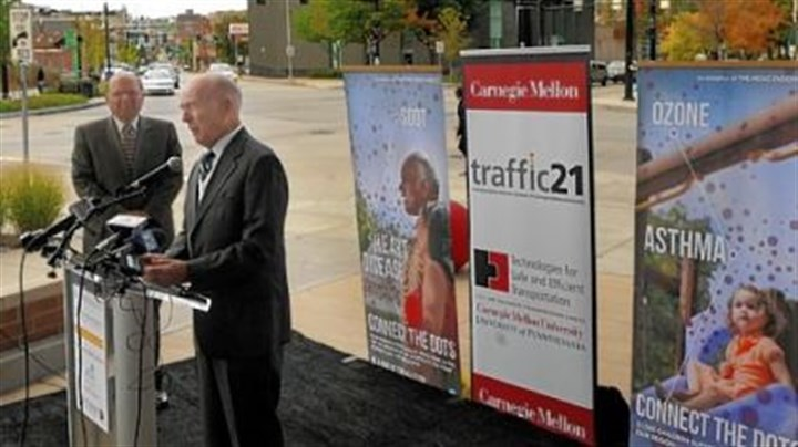 CMU Jared Cohon, president of Carnegie Mellon University, stands near as Henry Hillman speaks about CMU's first-of-its-kind traffic signal control system. A pilot project for the synchronized signals reduced vehicle wait time in the high-traffic sections of East Liberty by 40 percent. The event was held in front of the Target store near Penn Avenue and Penn Circle.