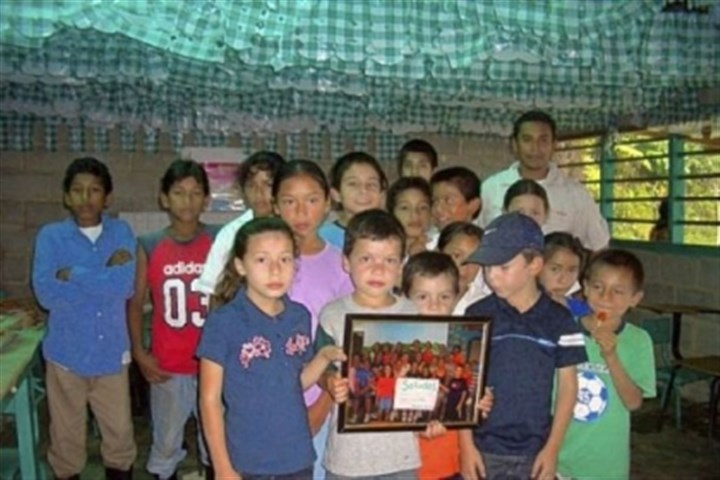 Coffee 2 Jose Daniel, back row far left, with elementary school classmates holding a picture of Neil Armstrong Student Council in 2007, the first year the Student Council sold coffee to raise funds for scholarships in Honduras.