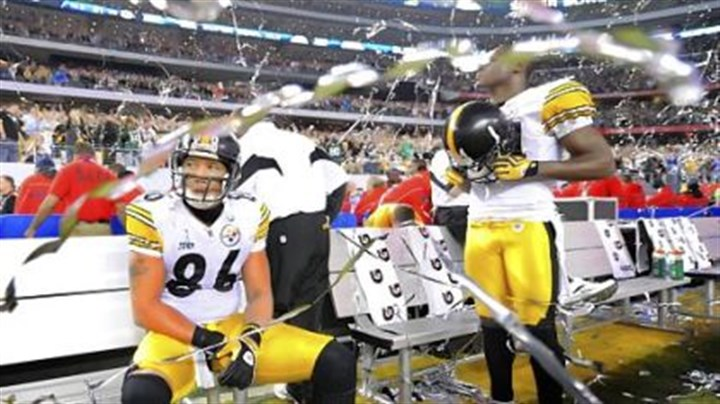 Confetti Steelers Hines Ward and Antonio Brown sit on the sidelines as confetti falls around them marking the Packers' victory in Super Bowl XLV.