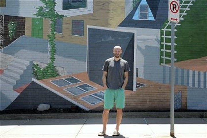 "'Connected' Will Schlough, 28, of Friendship, stands in front of his mural, ""Connected."""