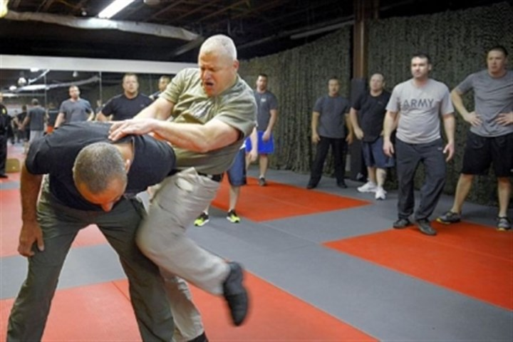 Cops 1 Deputy Sheriff Chris Galassi, left, and Sgt. Michael Davis of Los Angeles County Sheriff's De-partment show Krav Maga techniques to local police last Thursday at Wright's Gym in Crafton.