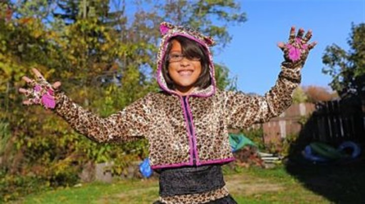 Costume Harmony Ziccardi, 8, shows of her leopard girl Halloween costume outside her home in Pleasant Hills on Tuesday.