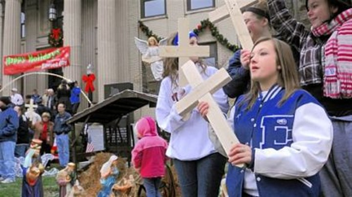 Cross Morgan Prokovich, right, 17, holds a wooden cross at a community demonstration Friday in favor of Ellwood City?s creche displayed on the lawn of the municipal building.