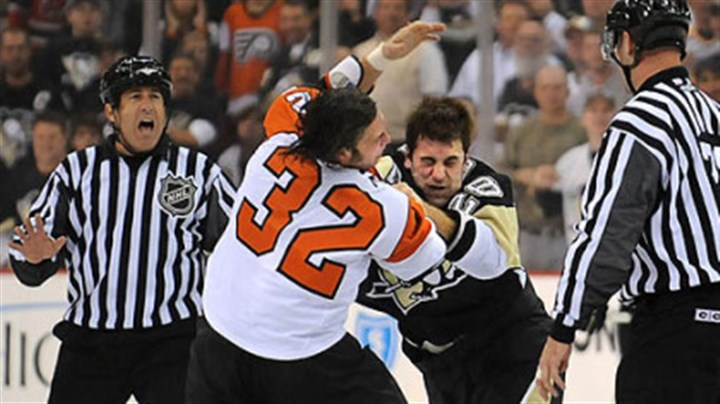 Cut it out, boys Eric Godard, right, and Philadelphia's Riley Cote squared off early in last night's game at Mellon Arena. Apparently, they aren't listening to the official.