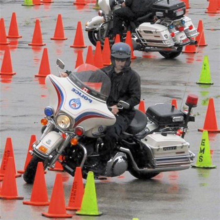 Cycles Officers practice their riding on a skills course made up of sets of orange cones at 26th and Sidney streets on the South Side on Thursday.