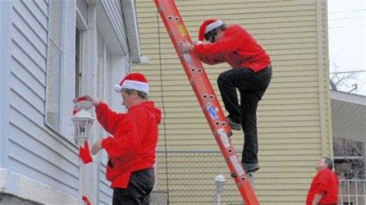 Decorate From left, Tammie Langston, Jake Colosimo and Ron Ventura, who work with Christmas Decor by E.L.F. Entertainment, decorate a home Saturday in South Oakland. The home is owned by James Chavis, who is on active duty in the Army. The company decorates homes for soldiers? families while they are deployed.