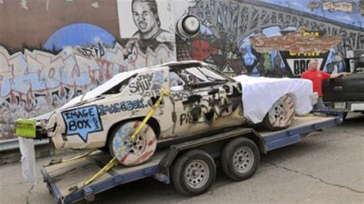 Demolition derby art car Jason Sauer, the founder of Most Wanted Gallery, stands with his demolition derby art car Thursday in Garfield.
