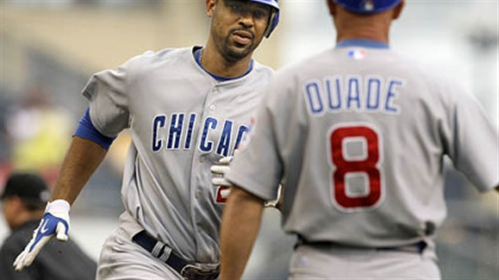 Derrek Lee and Mike Quade Cubs first baseman Derrek Lee rounds third to greetings from coach Mike Quade after hitting a solo homerun off Pirates pitcher Daniel McCutchen during the first inning.