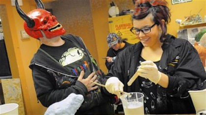 Devil instructor Wearing a red devil mask, instructor Shawn Ronzio of Tom Savini's Special Make-up Effects Program shares a laugh with Alana Schiro, 19, of New York at a sculpture class. The Savini program is part of the Douglas Education Center in Monessen.