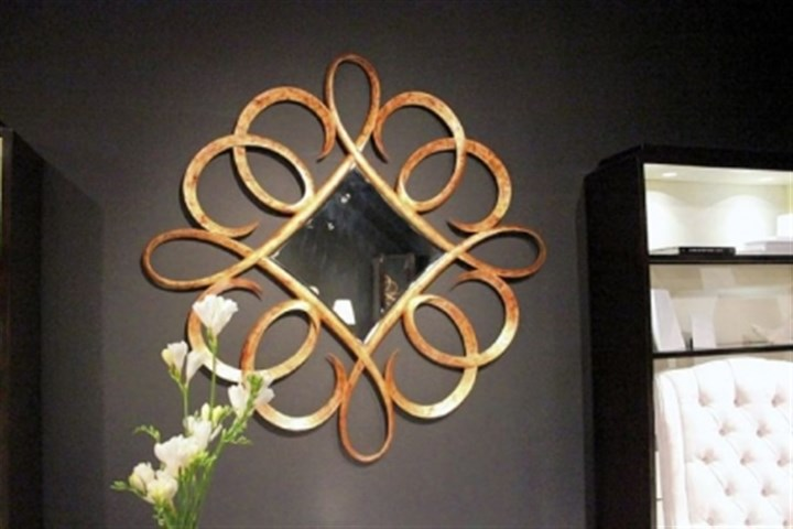 Diamond-shaped mirror Diamond-shaped mirror with floating curl detail carved from solid wood.