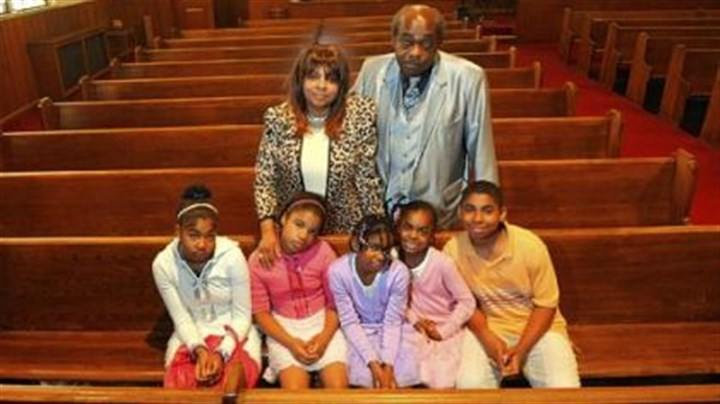 Dorothy Jean, Daniel Guy and their grandchildren Dorothy Jean Guy and her husband Daniel stand behind their grandchildren, from left, Lisa, Israel, Egypt, Destiny and Jonathan, at their church in Braddock on Sunday. Ms. Guy's grandson Danny is not pictured.