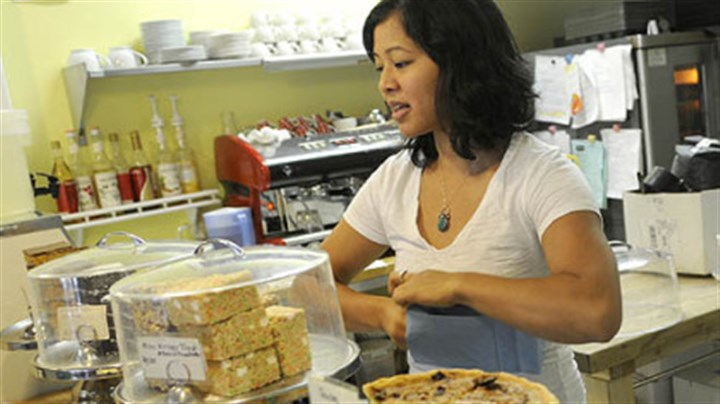Dozen Bake Shop Melissa Santos of Bloomfield bags a customer order at the Dozen Bake Shop in Lawrenceville. The shop has been using Twitter to let customers know what's new.