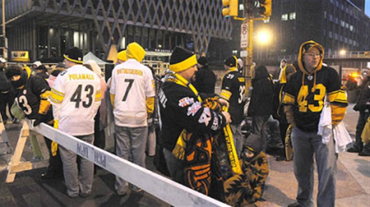 Early birds Steelers fans wait in the early morning hours for the prime spots near the grandstand at the Boulevard of the Allies at Stanwix Street.